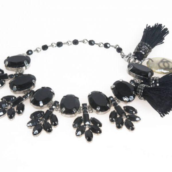 Piccolo bracciale con catena rosario alternata ad un elemento composto di ovali e piccole foglie in strass incastonati. Completano il bijoux tre nappine ricamate a mano.